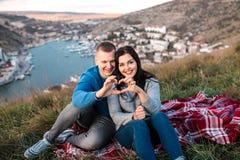 Los pares de amor hacen el corazón por los fingeres al aire libre fotografía de archivo libre de regalías
