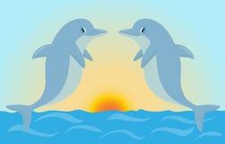 Los pares de delfínes lindos de la historieta que juegan en la puesta del sol se encienden Vecto Foto de archivo