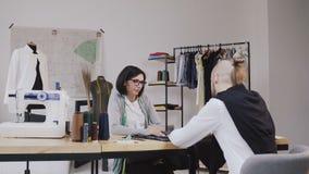 Los pares de diseñadores de moda están trabajando en taller La mujer joven atractiva en vidrios y el hombre barbudo elegante está almacen de metraje de vídeo