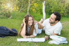 Los pares de estudiantes jovenes se divierten mientras que estudian en el parque Fotos de archivo libres de regalías