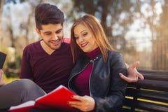 Los pares de estudiantes se están sentando en el banco en el parque Fotografía de archivo