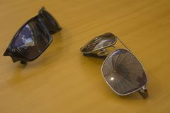 Los pares de gafas de sol mienten en una tabla de madera fotografía de archivo
