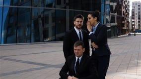 Los pares de hombres de negocios cotillean en la parte posterior del colega perjudicado almacen de metraje de vídeo