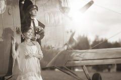 Los pares de la boda acercan a los aviones del vintage Foto de archivo