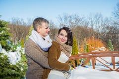Los pares de la boda en un llamativo marchitan día, caminando, divirtiéndose detrás del pino-árbol vestido de boda rústico del co Foto de archivo