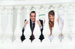 Los pares de la boda sonríen y miran hacia fuera del balaustre blanco Fotos de archivo