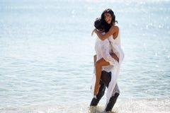 Los pares de la felicidad gozan en la playa, imagen atractiva de recienes casados locos, aislada en un mar Mediterráneo del agua  foto de archivo libre de regalías
