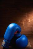 Los pares de los dos guantes de boxeo rojos mienten en la tabla de madera contra fondo de madera Fotografía de archivo