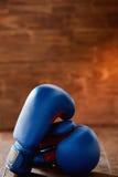 Los pares de los dos guantes de boxeo rojos mienten en la tabla de madera contra fondo de madera Fotografía de archivo libre de regalías