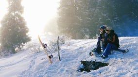 Los pares de los Snowboarders calientan por la hoguera al aire libre, montaña almacen de video