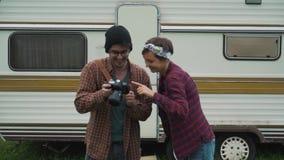 Los pares de los turistas que miran las fotos acercan a la caravana almacen de metraje de vídeo