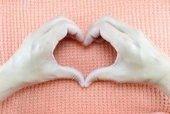 Los pares de manos que crean el corazón forman en fondo de punto de la tela Imagenes de archivo