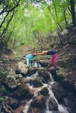Los pares de mujeres gozan en la naturaleza que se coloca en rocas en el pequeño soporte Fotos de archivo