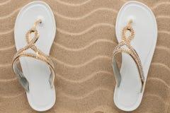 Los pares de sandalias blancas de la playa en diamantes artificiales se colocan en la arena Fotos de archivo