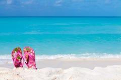 Los pares de sandalias coloreadas en una arena blanca varan Imágenes de archivo libres de regalías