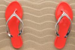 Los pares de sandalias rojas de la playa en diamantes artificiales se colocan en la arena Foto de archivo libre de regalías