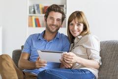 Los pares de treinta años en el app hacen tabletas la PC en hogar blanco moderno imagen de archivo libre de regalías