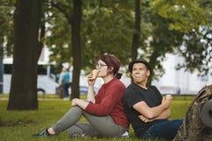 Los pares de los turistas de los adolescentes con las mochilas que comen el helado y tienen resto en el parque de la ciudad Fotos de archivo libres de regalías