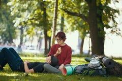 Los pares de los turistas de los adolescentes con las mochilas tienen resto en el parque de la ciudad Imagen de archivo libre de regalías