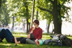 Los pares de los turistas de los adolescentes con las mochilas tienen resto en el parque de la ciudad Fotos de archivo libres de regalías