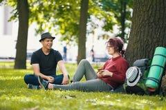 Los pares de los turistas de los adolescentes con las mochilas tienen resto en el parque de la ciudad cerca de árbol grande Imagen de archivo libre de regalías