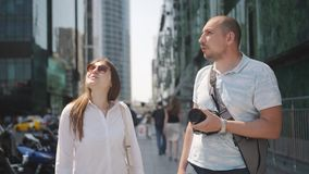 Los pares de turistas caminan a través de la pieza del negocio de la metrópoli, y admiran los rascacielos modernos y fotografiado almacen de metraje de vídeo