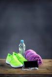 Los pares de verde amarillo se divierten pone y los auriculares elegantes del agua de la toalla de los zapatos en el tablero de m Foto de archivo