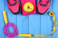 Los pares de zapatos del deporte, de manzana fresca y de accesorios para la aptitud en tableros azules copian el espacio para el  Fotografía de archivo libre de regalías