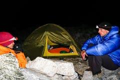 Los pares del escalador de montaña se sientan fuera de una tienda en la oscuridad y beber té arriba para arriba en el Blanca de C fotos de archivo