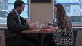 Los pares del negocio disfrutan de la comida del almuerzo en el café almacen de video