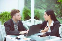 Los pares del negocio joven que trabajan en la oficina moderna, dos compañeros de trabajo que discuten la diversión proyectan sob Fotografía de archivo
