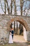 Los pares del recién casado presentan en la vieja puerta arruinada de la pared barroca antigua del castillo Fotografía de archivo
