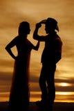 Los pares del vaquero colocan la silueta su mano en el sombrero Imágenes de archivo libres de regalías