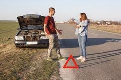Los pares discuten en el camino, hacen que el problema con brocken el coche, siendo en pánico, ponen el ` t conocen qué hacer, tr fotos de archivo libres de regalías