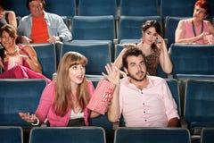 Los pares discuten en un teatro Imágenes de archivo libres de regalías