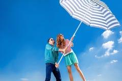 Los pares divertidos y jovenes se divierten con el parasol de playa en el cielo azul Imagen de archivo