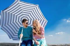 Los pares divertidos y jovenes se divierten con el parasol de playa en el tejado Imagen de archivo libre de regalías