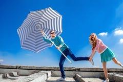 Los pares divertidos y jovenes se divierten con el parasol de playa en el tejado Fotografía de archivo libre de regalías