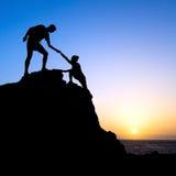 Los pares, el hombre y la mujer ayudan a la silueta en montañas Fotografía de archivo