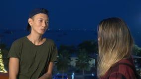 Los pares, el individuo y la muchacha asiáticos hermosos jovenes están hablando con uno a, colocándose en la calle de la ciudad almacen de metraje de vídeo