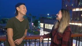 Los pares, el individuo y la muchacha asiáticos hermosos jovenes están hablando con uno a, colocándose en la calle de la ciudad metrajes