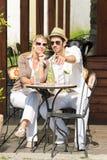 Los pares elegantes de la terraza del restaurante beben día asoleado Fotografía de archivo