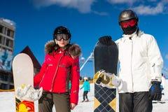 Los pares elegantes jovenes en trajes de esquí, cascos y gafas del esquí se colocan Imagenes de archivo