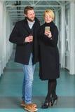 Los pares elegantes se vistieron en la capa que miraba en el teléfono elegante el pasillo Foto de archivo libre de regalías
