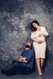 Los pares embarazadas jovenes felices en el estudio en un fondo oscuro concepto de la relación de familia fotos de archivo