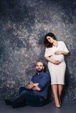Los pares embarazadas jovenes felices en el estudio en un fondo oscuro concepto de la relación de familia fotos de archivo libres de regalías