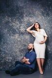 Los pares embarazadas jovenes felices en el estudio en un fondo oscuro concepto de la relación de familia imagen de archivo