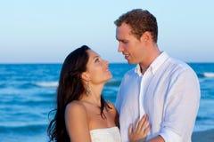 Los pares en amor abrazan en vacaciones azules del mar Imagenes de archivo