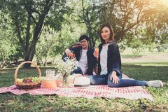 Los pares en amor beben un zumo de naranja en la comida campestre del verano, ocio, h Imagenes de archivo