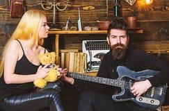 Los pares en amor en caras relajadas disfrutan de la atmósfera romántica Sirva la guitarra del juego mientras que la señora sosti fotografía de archivo libre de regalías